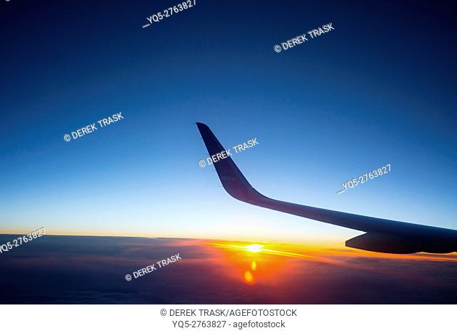 airplane flying into the Midnight Sun en route to Iceland