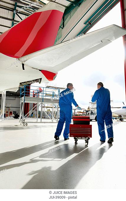 Engineers rolling tool box on cart below tail of passenger jet in hangar