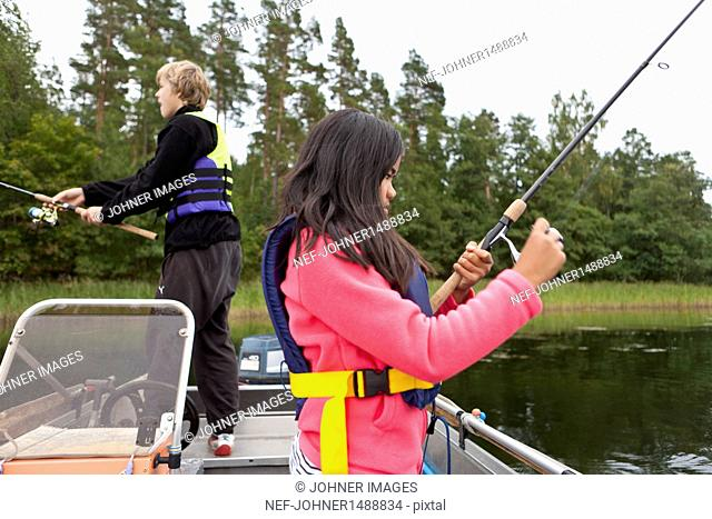 Brother and sister fishing from boat