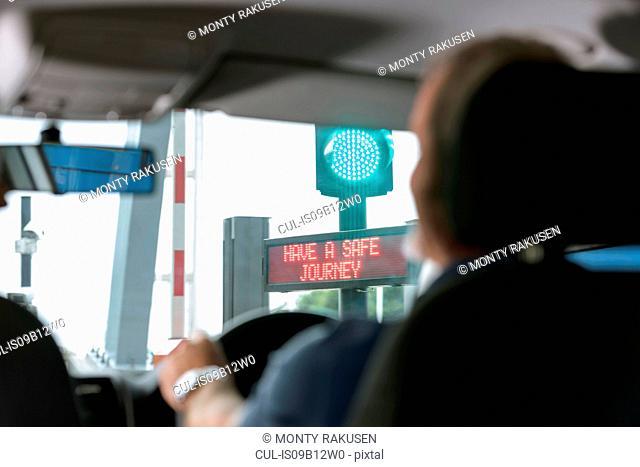 Man driving through signals at toll booth at bridge toll