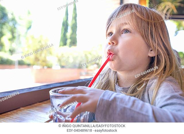 Portrait of three years old blonde cute caucasian child, with gray shirt, drinking water with red straw from crystal glass next to window at restaurant