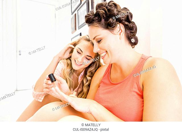 Two female friends sitting together, painting fingernails