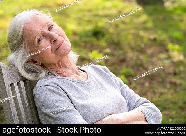 Thoughtful senior woman relaxing in garden