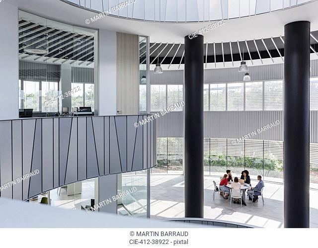 Business people meeting at table in architectural, modern office atrium