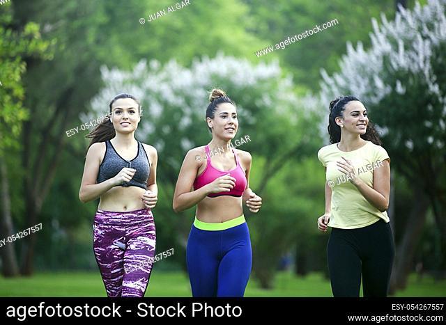 Portrait of happy girlfriends running in summer park of Cordoba, Spain