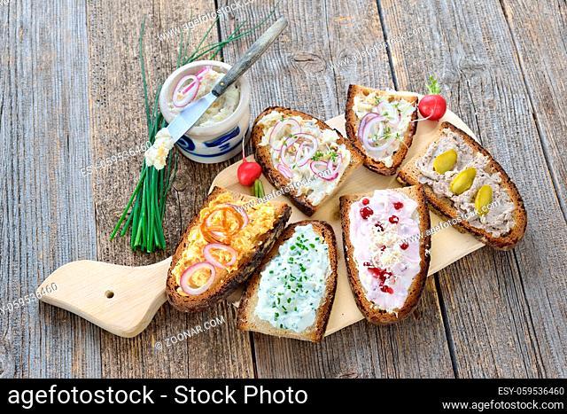 Brotaufstriche auf rustikalem Bauernbrot: Griebenschmalz, Obatzda, Schnittlauchquark, Preiselbeer-Meerrettich-Quark und Landleberwurst - Hearty Bavarian snack:...