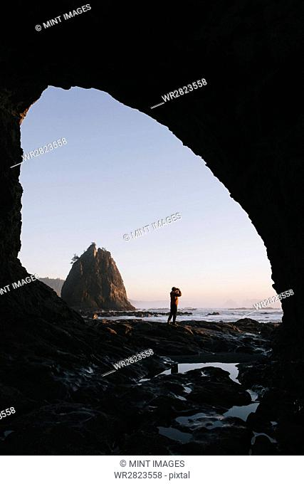 Man standing beneath sea cave at dusk, using binoculars at Hole-in-the-Rock, Rialto Beach, Olympic National Park, Washington, USA