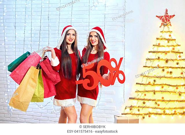 Horizontal shot of two happy young snow maidens in CHritmas outfits posing with shopping bags and -50 discount sign copyspace consumerism seasonal sale retail...