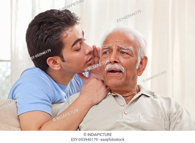 Grandson whispering into grandfather's ear