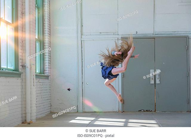 Teenage girl with long brown hair leaping mid air in dance studio