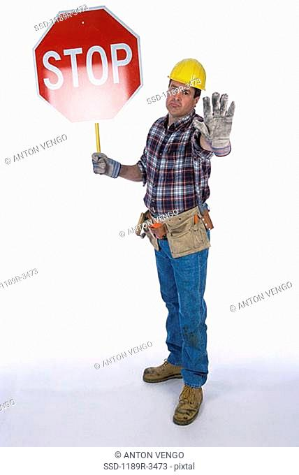 Portrait of a worker standing with a stop sign