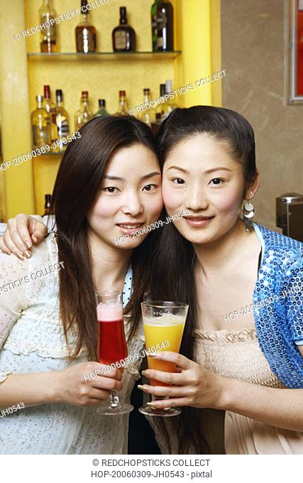 Portrait of a teenage girl and a young woman holding drinks