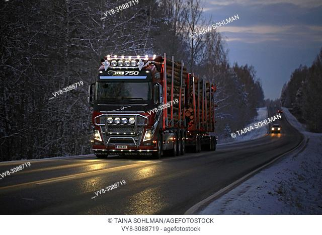 Customized Volvo FH16 750 logging truck of R. M. Enberg Transport Ab lights up the road as it hauls log load through rural landscape on a dark winter evening