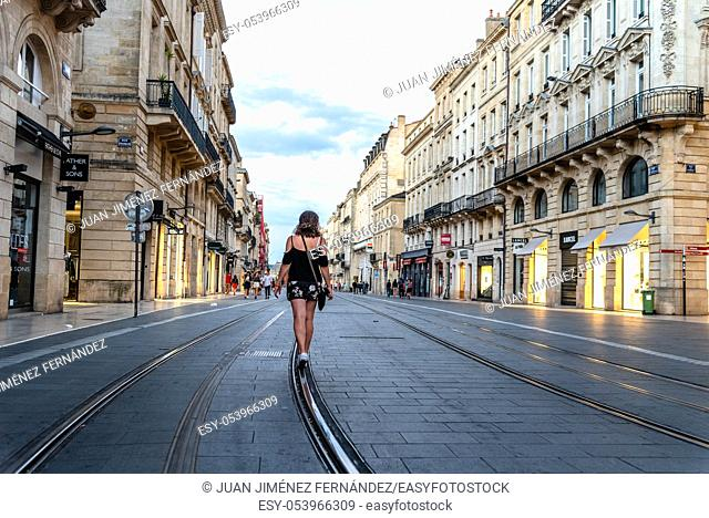 Bordeaux, France - July 22, 2018: Woman walking on the tram tracks in pedestrian street in historic centre of the city. Cours de l'Intendance
