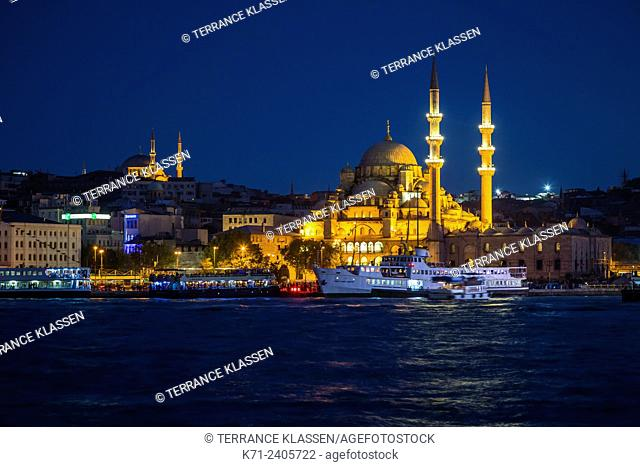 The New Mosque illuminted at night with reflections in the Golden Horn in Istanbul, Turkey, Eurasia