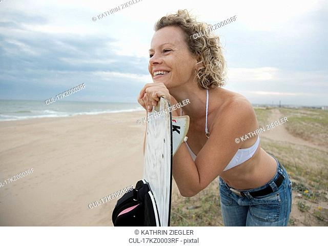 woman with kite board, overlooking beach