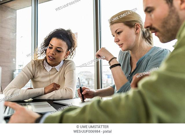 Three colleagues in office working together