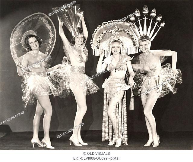 Four women wearing funny hats and costumes