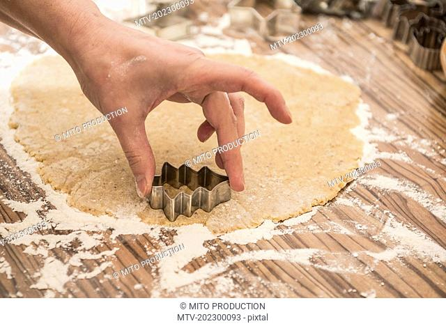 Close-up of a woman cutting out fir tree shape cookies, Munich, Bavaria, Germany