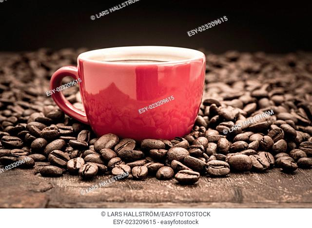 Closeup of dark roasted coffee beans and a red cup filled with fresh hot coffee. Food and drink backdrop showing aromatic and beautiful coffee beans