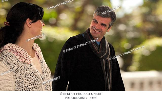 dolly shot of mid aged couple walking in park