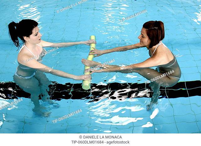 Women in swimming pool doing pilates exercise
