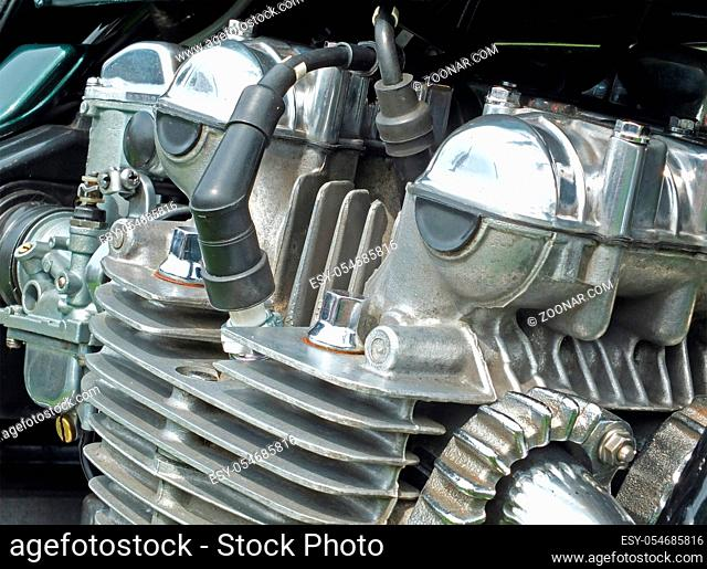 close up of a large of a large old motorcycle engine on a black frame with shiny chrome bolts and pipes