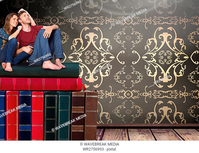 Couple sitting on Books stacked by wallpaper antique decorative