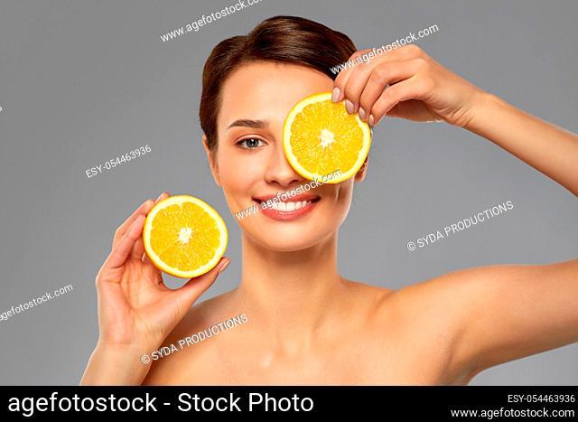 beautiful woman making eye mask of orange slices