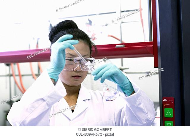 Female scientist using pipette and volumetric flask in lab