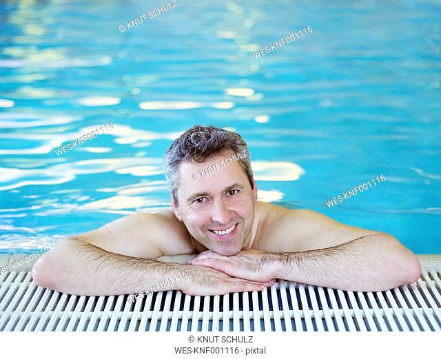 Germany, Hamburg, Mature man in swimming pool, smiling, portrait