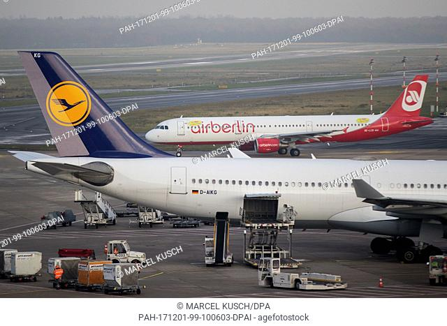A plane of the bankrupt airline Air Berlin with a sticker of Niki airline rolls along the runway past a plane of Lufthansa at the airport in Duesseldorf