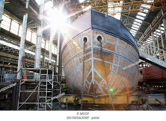 View of sunlit boat hull in shipyard workshop