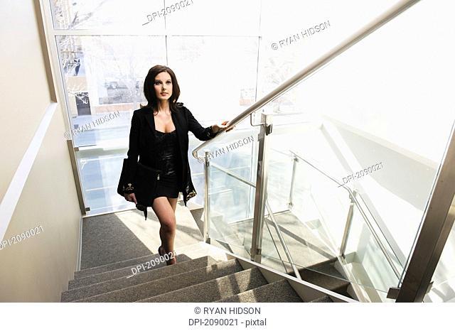 A young businesswoman climbing the steps, edmonton, alberta, canada