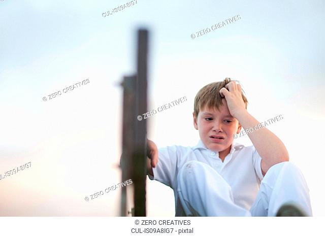 Boy on bleachers at cricket pitch scratching head