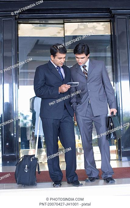 Two businessmen standing in front of the door of a hotel and looking at a mobile phone