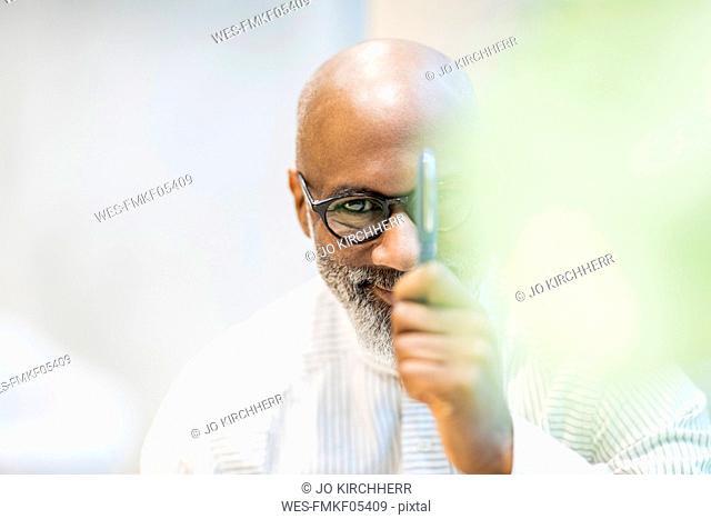 Portrait of bald businessman with pen