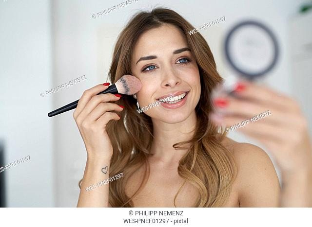 Smiling young woman applying make-up