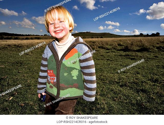 England, Hertfordshire, Hitchin. A cheerful two year old boy standing in a field