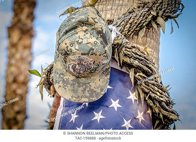 A US Marine hat hangs off a palm tree at the Welcome to Las Vegas Sing two weeks after the October Shooting in Las Vegas, NV