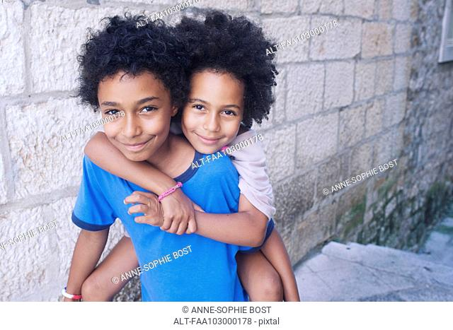 Young siblings embracing outdoors, portrait