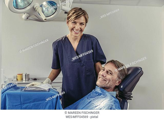 Dental surgeon talking to patient before treatment