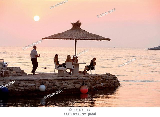 Waiter serving tourists at coastal restaurant table at sunset, Loviste, Croatia