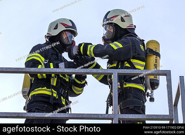 09 September 2021, Saxony, Pirna: Two firefighters prepare by checking each other's oxygen line on the protective mask. Fire brigades from the Sächsische...