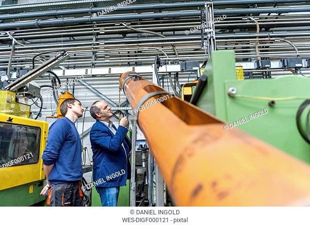 Two people in plastics factory examining machines