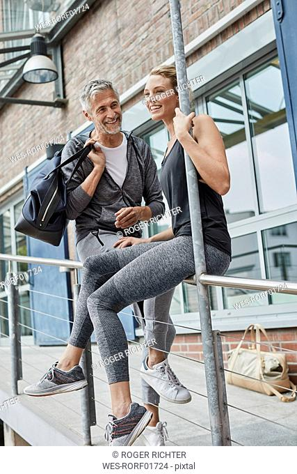 Portrait of mature man with sports bag and laughing young woman in front of gym