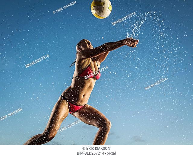 Water splashing on Caucasian woman playing volleyball