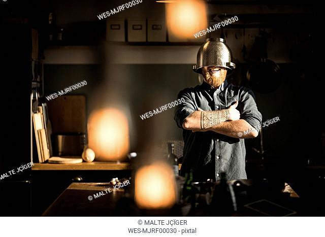 Man standing in kitchen, wearing colander as helmet