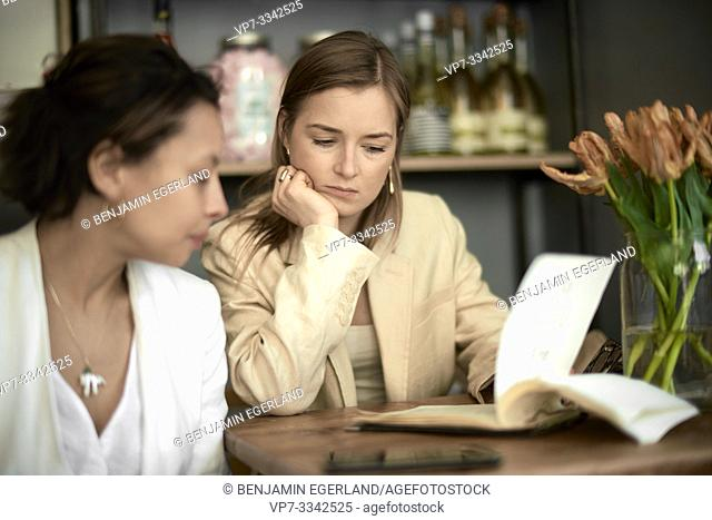 reluctant woman looking at menu card in restaurant