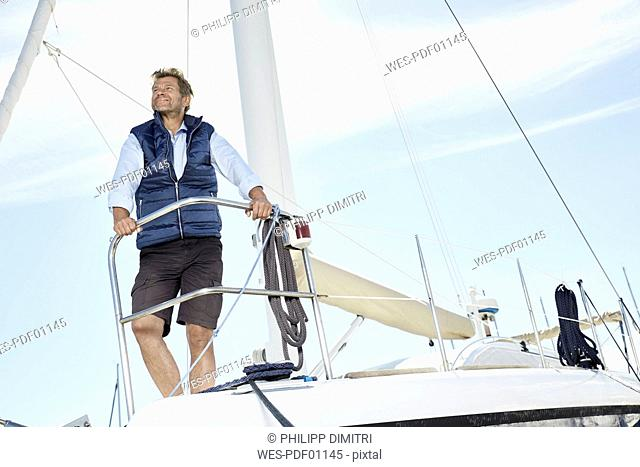 Portrait of smiling mature man on his sailing boat looking at distance